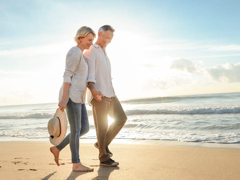 retire couple walking on the beach